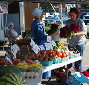 A customer buys flowers from the Pleasant Lane Farm stand at Thursday West Side Farmers Market.