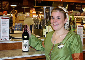 Manager Audree Riesterer, dressed for Halloween, offers tasting pours of Lone Oak Merlot at Whole Food Market's wine bar.