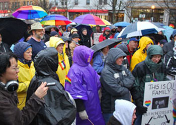 The crowd listens to Sandi Smith speak before the march begins. Larry Kestenbaum, Washtenaw County clerk, is the tall guy in the khaki hat.