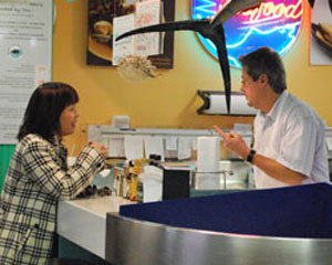 Mike Monahan, owner of Monahan's Seafood Market, talks to a customer.