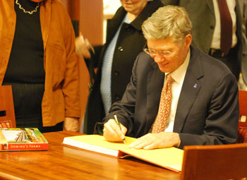 Tom Monaghan signs a copy of Domino's Farms: A Landmark Office Park in the Country