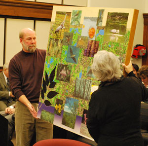 "and artist Leslie Sobel hold one of four panels from the ""Ecology of Place"""