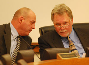 Rolland Sizemore, right, newly elected chair of the Washtenaw County Board of Commissioners, confers with Curt Hedger, the countys corporate counsel, at Wednesday nights board meeting.