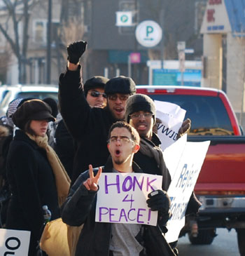 Some drivers headed through the intersection responded to the sign by honking and waving.