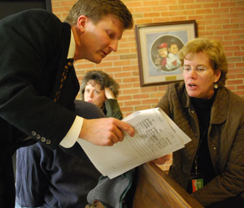 Scott Munzel, attorney for Alex de Parry on the City Place PUD application, discusses the signatures on the petition with Jayne Miller, director of community services with city of Ann Arbor.  Eagle-eyed readers of the Chronicle will know what kind of pass is hanging around Miller's neck.