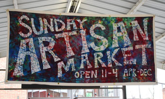 The Sunday Artisan Market banner, made by artist Cheri Reiman, who sells tie-dye work at the market.