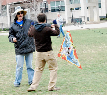 Two guys goofing off with a kite in a field