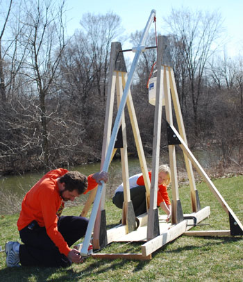 Two people loading the projectile for a trebuchet.