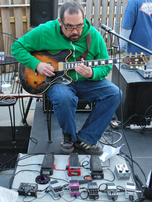 Guy in green shirt with guitar and several pedals