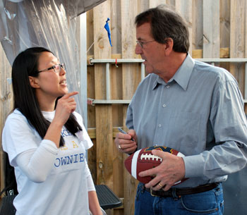 Woman standing next to Lloyd Carr getting a football signed for her boyfriend.