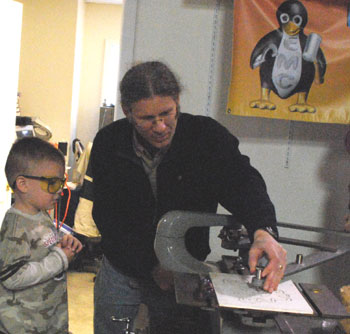 Kid with safety glasses watching an etching in progress.