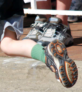 foot wearing green socks in running shoes in full stride