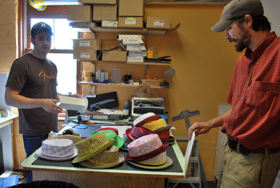 Evan Perich, left, is working on a display for a line of hats that his father is designing with the Swedish firm Wigens.