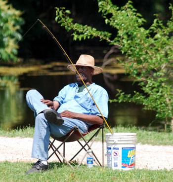 fisherman sitting in a chair on the bank of Argo Pond at the dam