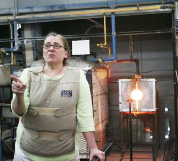 Annette Baron, owner and founder of Baron Glassworks, explains glassblowing safety guidelines to a group of visitors in her studio. Two pieces of heating equipment stand behind her a furnace for storing molten glass and a glory hole for reheating glass during the shaping process.