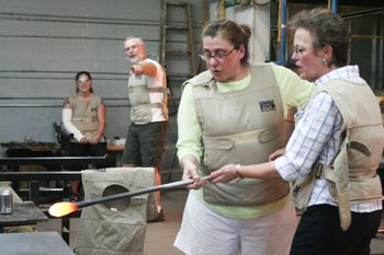 Baron Glassworks owner Annette Baron, left, guides Pam Roselle in making a glass garden ball, while Baron Glassworks employee Jim Fry points out the technique to another visitor preparing to try glassblowing.
