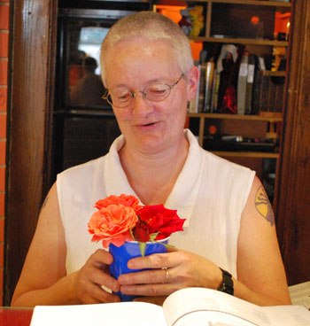 Jerri Dodge, who manages the bookstore, with some flowers brought in by a customer.