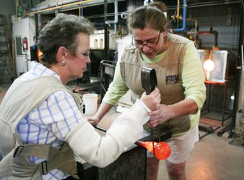 Baron Glassworks owner Annette Baron guides Pam Roselle in shaping the molten glass using jacks.