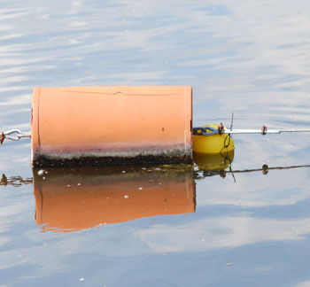 Big orange buoy floating next to small yellow buoy on Argo Pond in Ann Arbor Michigan