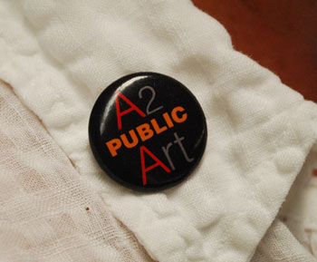 A button promoting public art, on the lapel of Cathy Gendron, a member of the Ann Arbor Public Art Commission.