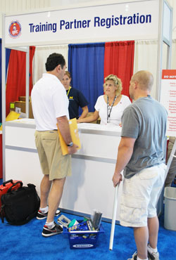 Denise Jenkins, assistant NTI coordinator, helps two trade show vendors check in.