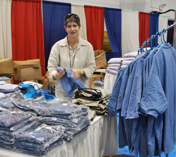 Michelle Spivey hangs shirts with the embroidered NJATC logo. Her nametag states