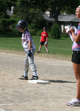 Katrina Sadis gets ready to run as Rebecca Friedman coaches from beside first base.