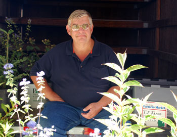 Dave Barkman, the newest member of the Ann Arbor Public Market Advisory Commission, sitting on the back of his truck at Wednesdays farmers market.