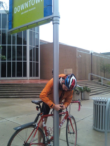 cyclist locking bike to a pole