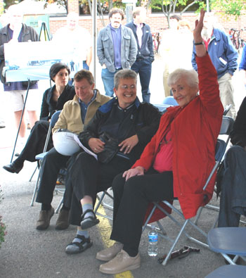 four people seated in chairs, woman in red coat raises her hand
