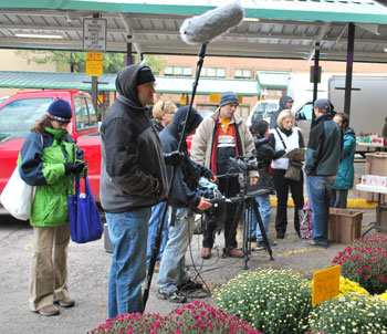 "A film crew for ""Naked Angel"" was shooting at Wednesday's farmers market. The director, Christina Morales Hemenway, is at the far right in a white vest."