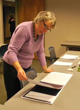 Margaret Parker, chair of the Ann Arbor Public Art Commission, looks over drawings by Herbert Dreiseitl before the start of a special meeting on Monday night at the City Center Building's 7th floor conference room.