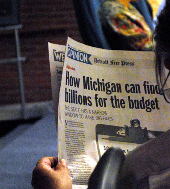 over the shoulder shot of someone reading a newspaper with the headline How Michigan can find  billions for the budget