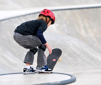kid in red helmet with skateboard about to launch down a bowl