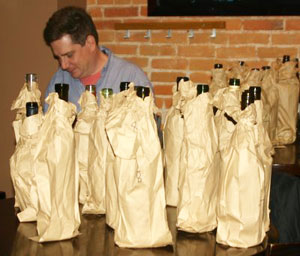 Wine Clash organizer Andrew Hall, behind a gaggle of paper-bagged wines.