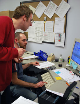 Matt Yankee, at the computer, shows Jason Brooks how to enter data into the election software program. Both are deputy clerks with Washtenaw County.