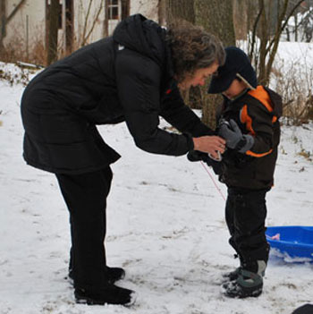 Kirsten Levinsohn helps a little sledder with his coat.