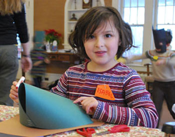 Isabel Ahbel-Rappe worked on her Happy New Year's hat on Thursday at the Leslie Science and Nature Center's holiday break camp.