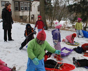 Kirsten Levinsohn, executive director of Leslie Science and Nature Center, watches as kids in the holiday break camp go sledding.