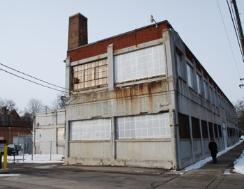 The vacant building on city-owned property at 415 W. Washington. This view is looking west – an entrance to a surface parking lot is in the foreground.