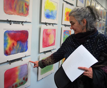 Diane Black, a member of the public market advisory commission, also teaches kindergarten at Rudolf Steiner School. She points out a painting by one of her students, Fionnuala, whose father Rob MacKercher, is a vendor at the Ann Arbor Farmers Market.