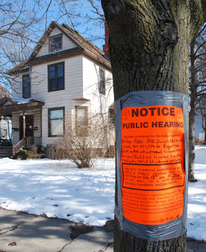 A public hearing notice duct-taped to a tree