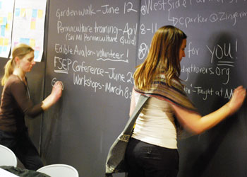 Two women writing on a chalkboard