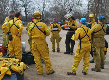Staff and volunteers in yellow fire suits stand in a circle