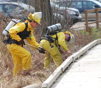 Two men in fire gear spray water on the Argo Pond boardwalk