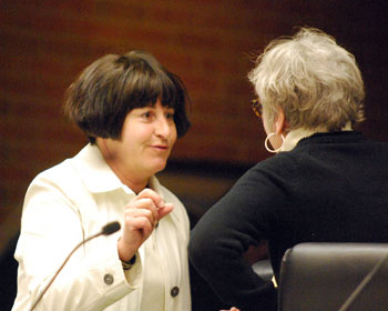 Jane Lumm (Ward 2) talks to Kathe Wunderlich (back to camera) before the council meeting. Wunderlich has worked as part of a citizens group opposing the runway extension.