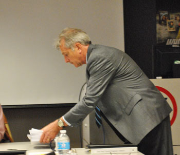 AATA strategic planner Michael Benham sets a stack of draft reports on the table at the April 26 special board meeting.