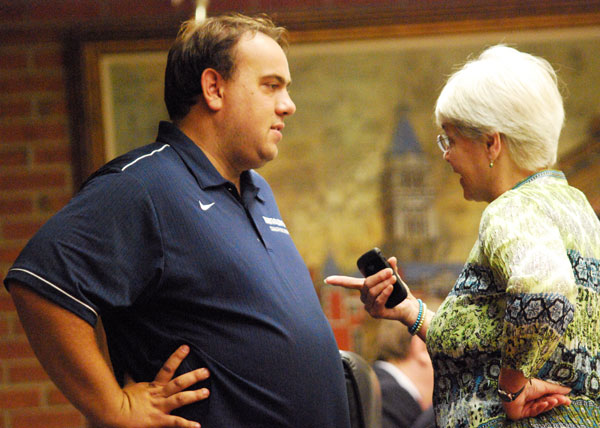 Eric Sturgis talks with Ward 2 councilmember Marcia Higgins before the city council's June 18, 2012 meeting.