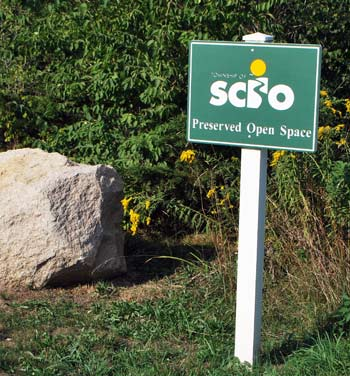 Sign signifying a partnership between Scio Township land preservation efforts and the county natural areas preservation program