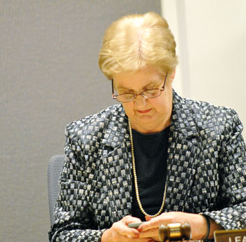 DDA board chair Leah Gunn checks her smart phone before the start of the Nov. 7 meeting.